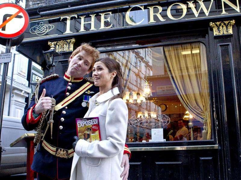 Lookalikes of Prince Harry and Pippa Middleton, stop outside the Crown Pub during a 'Royal walkabout' in central London, to launch the new book, Exposed, by a British artist and photographer Alison Jackson. AP Photo