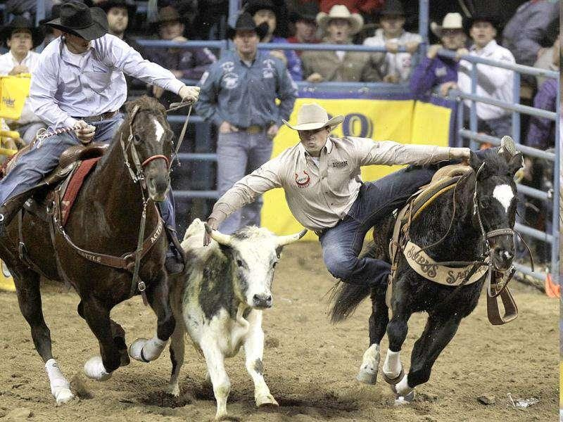 Olin Hannum of Malad, Idaho, competes in the steer wrestling event during the seventh go-round of the National Finals Rodeo in Las Vegas.