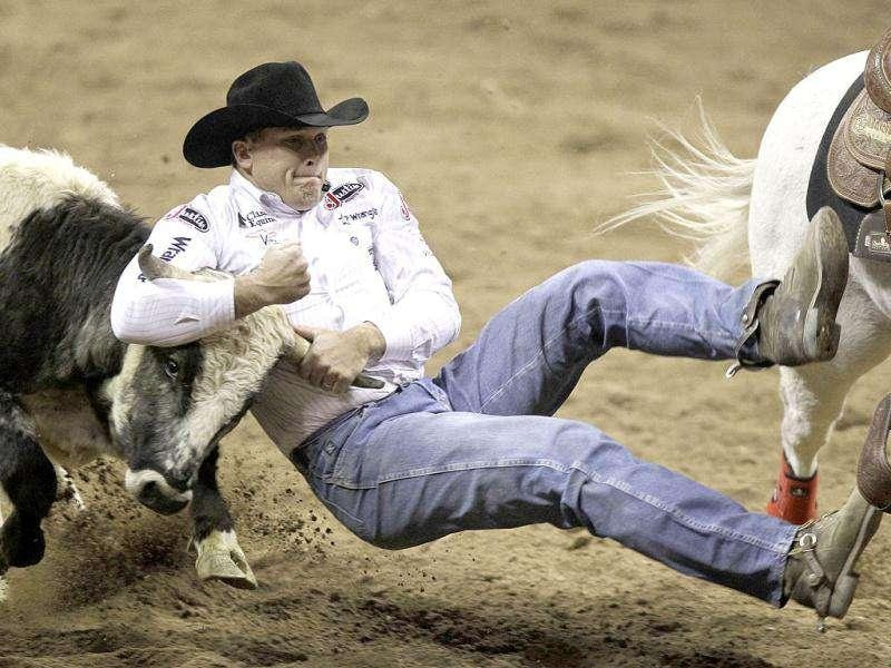 Dean Gorsuch of Gering, Neb., pulls down a steer during the steer wrestling event in the seventh go-round of the National Finals Rodeo in Las Vegas.