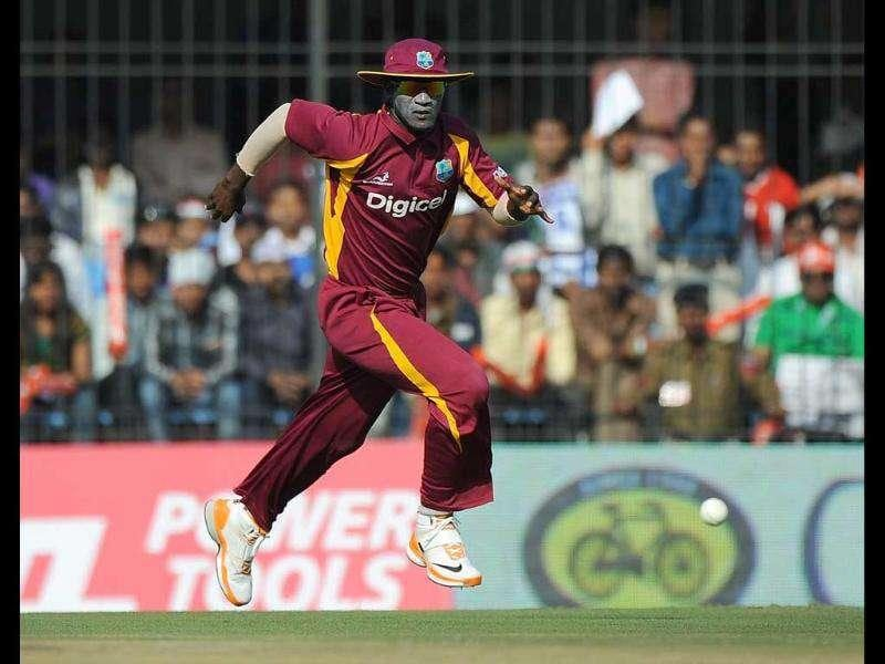 West Indies captain Darren Sammy runs to catch a ball during the fourth one-day international cricket match at The Holkar Stadium in Indore. AFP Photo