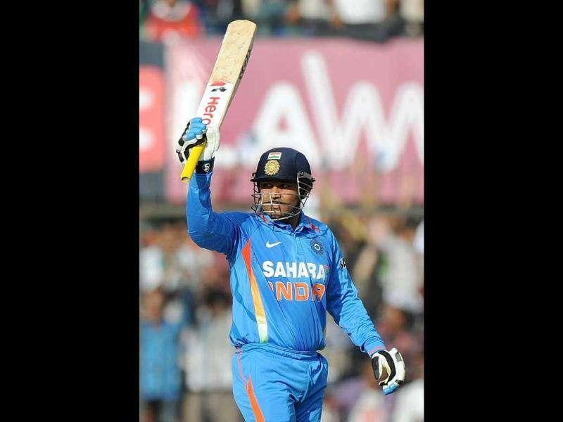 Virender Sehwag celebrates after scoring an half century during the fourth ODI in Indore. AFP Photo