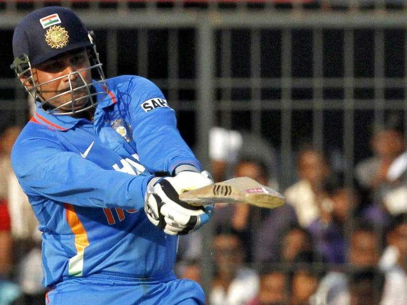 Virender Sehwag celebrates scoring his century during their fourth ODI against West Indies in Indore. Reuters Photo