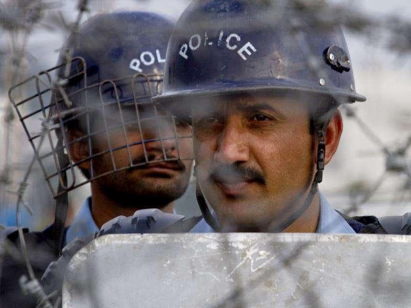 Pakistani police officers stand guard behind a barbed wire as they look towards protestors during an anti Nato rally in Islamabad, Pakistan. AP Photo/Anjum Naveed