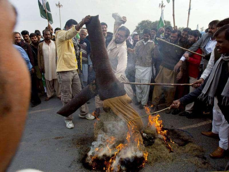 Angry Pakistanis beat a burning symbolic effigy of Nato during an anti Nato rally in Islamabad, Pakistan. AP Photo/Anjum Naveed