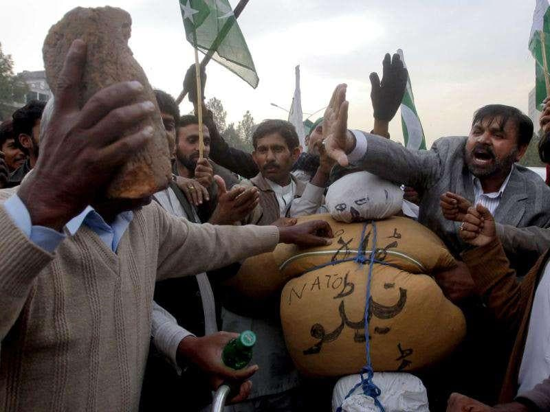 A man hits an effigy effigyrepresenting the Nato with a brick before setting it to fire during a rally in support of Pakistan army in Islamabad. Reuters/Faisal Mahmood