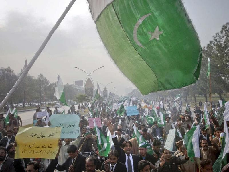 The Pakistan flag waves in the foreground as protesters hold placards during a rally in support of Pakistan army in Islamabad. The placard reads in Urdu