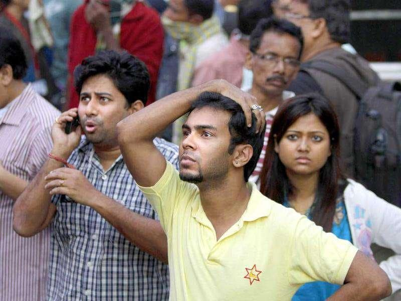 People stand outside AMRI hospital after it caught fire in Kolkata.