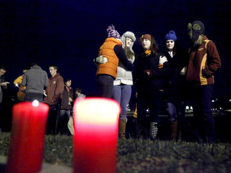 Students participate in an impromptu candlelight vigil in front of the 4/16 memorial on the campus of Virginia Tech after two shootings on the campus in Blacksburg, Va. (AP Photo/Steve Helber)