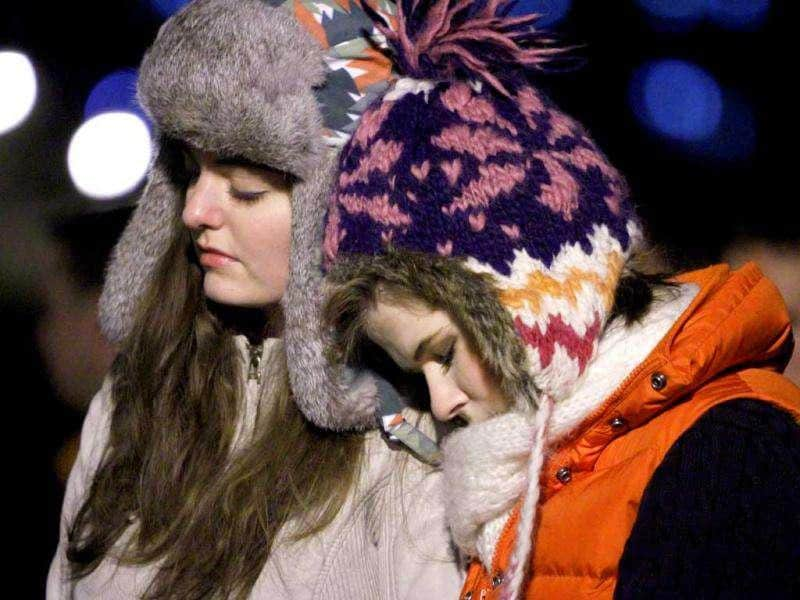 Virginia Tech freshmen, Massie Cashion (L) and Kasey Kraft, both from Alexandria, participate in an impromptu candlelight vigil in front of the 4/16 memorial on the campus of Virginia Tech after two shootings on the campus in Blacksburg, Va. (AP Photo/Steve Helber)