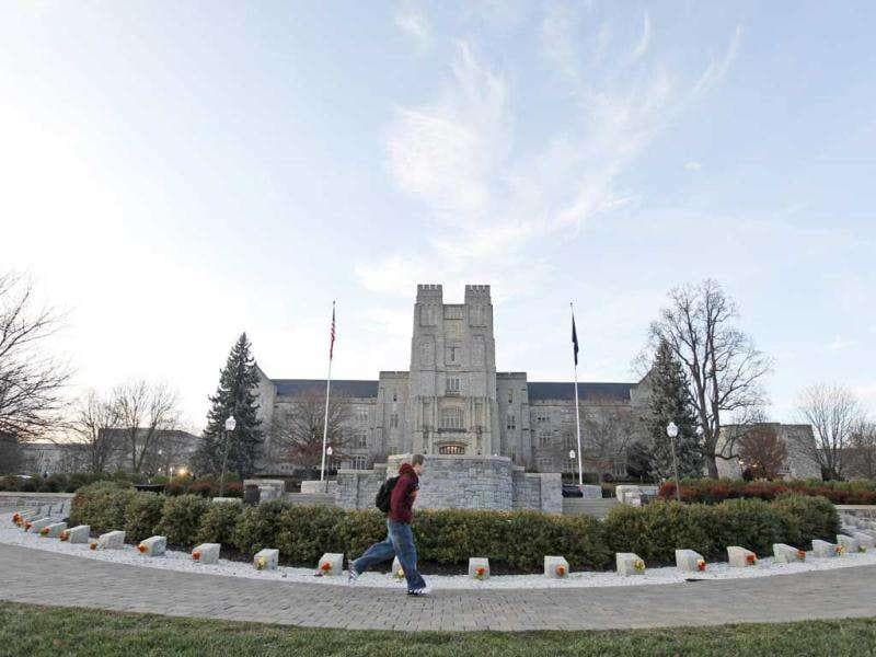 A Virginia Tech student runs past a memorial for the 2007 shooting victims after school officials declared the campus safe from an earlier shooting in Blacksburg, Va. (AP Photo/Steve Helber)