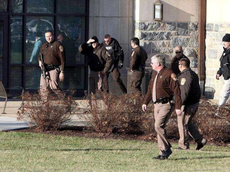 Law enforcement officers search the Virginia Tech campus near Washington Street after a multiple shooting left two people dead on campus in Blacksburg, Va. (AP Photo/The Roanoke Times, Kyle Green)