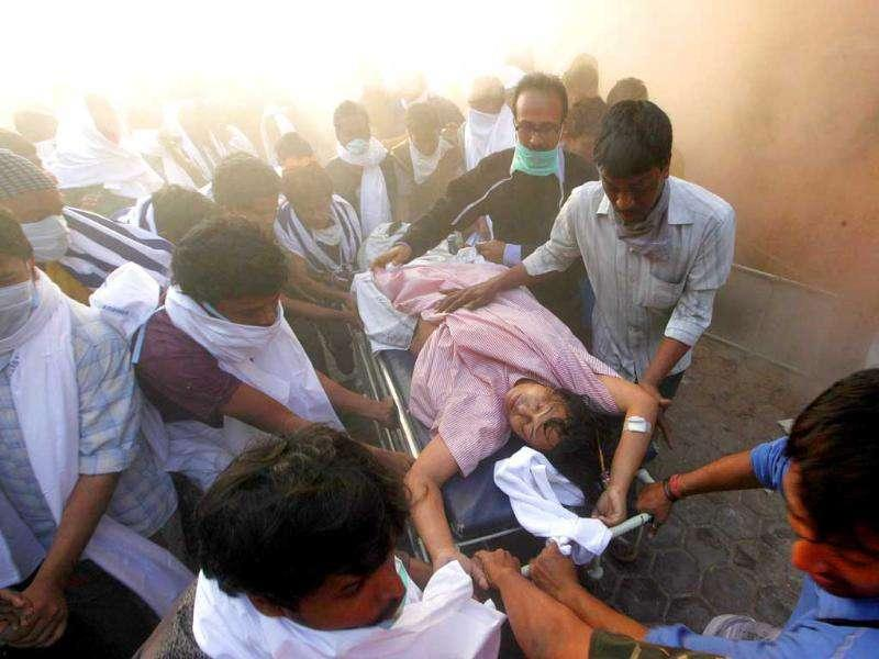 Rescuers carry a patient on a stretcher out of AMRI hospital after it caught fire in Kolkata.