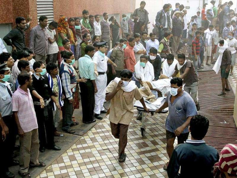 People help carry a patient out of AMRI hospital after it caught fire in Kolkata.
