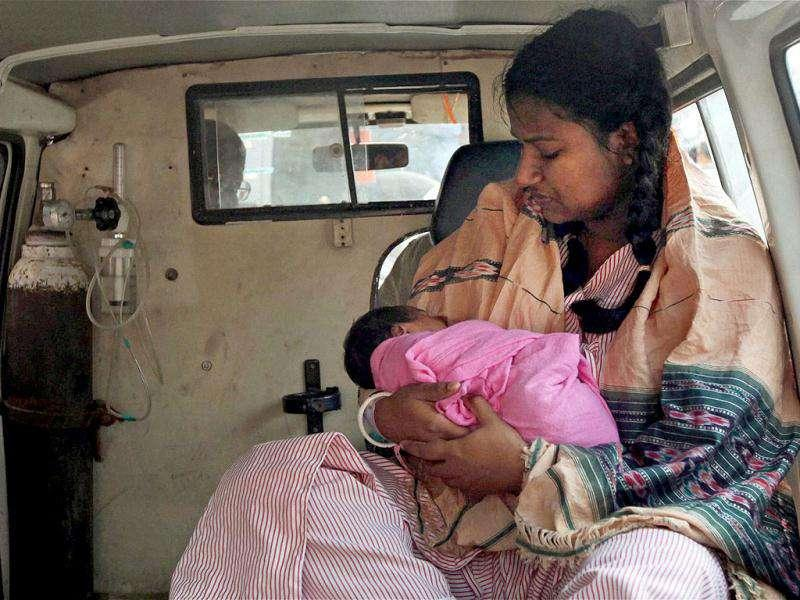 A rescued woman with her new born baby sitting in an ambulance after a major fire at AMRI hospital in Kolkata.