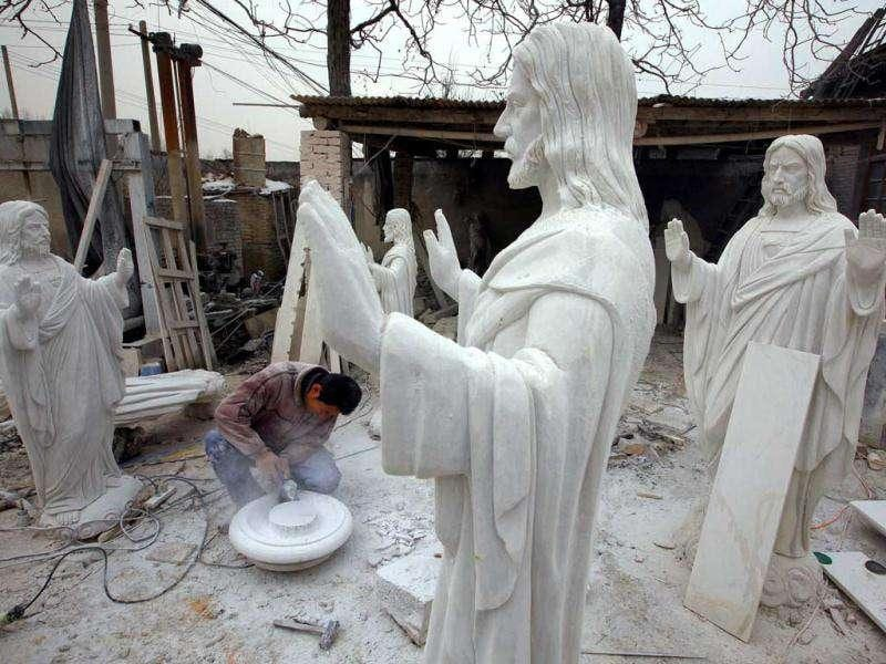 A sculptor works on statues of Jesus Christ in an outdoor workshop in the town of Dangcheng in Quyang county, southwest of Beijing. (Reuters/David Gray)