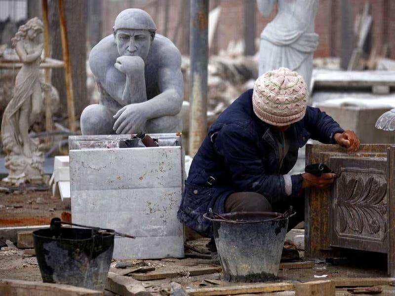 A woman washes a stone pillar while being surrounded by statues in an outdoor workshop in the town of Dangcheng in Quyang county, located 250 km (155 miles) southwest of Beijing. (Reuters/David Gray)