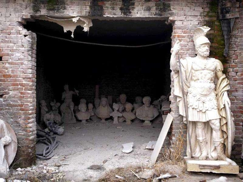 Completed statues rest inside and outside the entrance to a shed at an outdoor workshop in the town of Dangcheng in Quyang county, 240 km (150 miles) southwest of Beijing. (Reuters/David Gray)