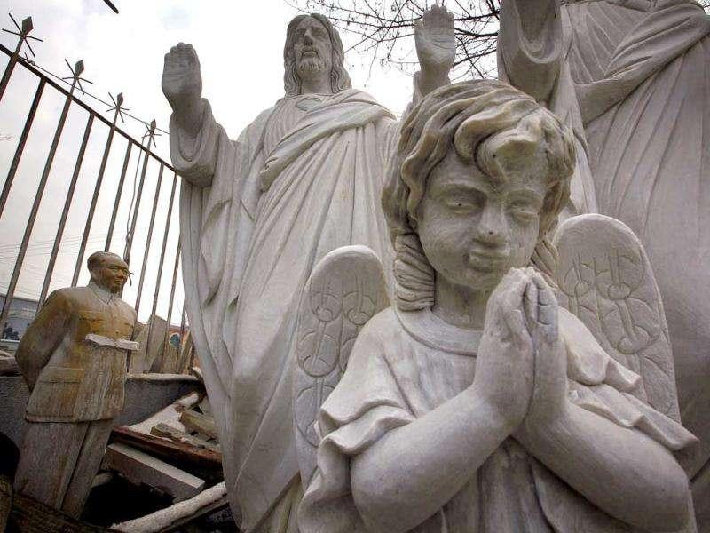 Statues of an angel (front), Jesus Christ and late Chinese leader Mao Zedong (L) rest at an outdoor workshop in the town of Dangcheng in Quyang county, 240 km (150 miles) southwest of Beijing. (Reuters/David Gray)