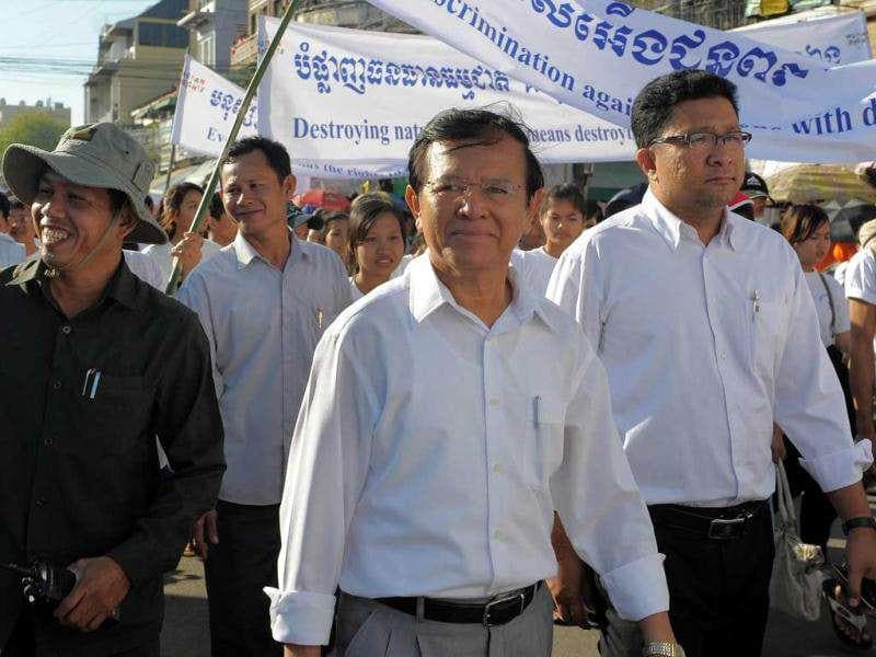 Cambodian president of the Human Rights Party Kem Sokha (C) attends a march along a street during the 63rd Anniversary of Human Rights day in Phnom Penh. AFP/Tang Chhin Sothy