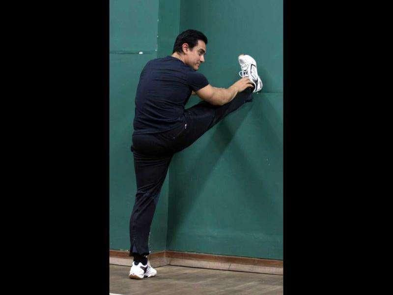 Aamir Khan stretches before an exhibition game of badminton during the book launch.