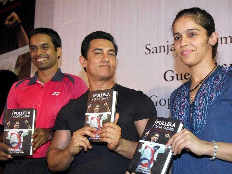 Badminton player Pullela Gopi Chand poses with Aamir Khan and Badminton star Saina Nehwal during the unveiling of Chand's biography