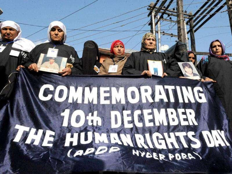 Member of the Association of Parents of Disappeared Persons (APDP) hold a banner and portraits of missing relatives during a demonstration to mark International Human Rights Day in Srinagar. AFP/Rouf Bhat