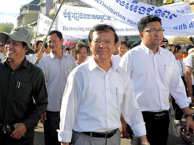 Cambodian president of the Human Rights Party Kem Sokha (C) attends a march along a street during the 63rd Anniversary of Human Rights day in Phnom Penh. Cambodian civil society in collaboration with international NGO's celebrated the Human Rights day under the theme