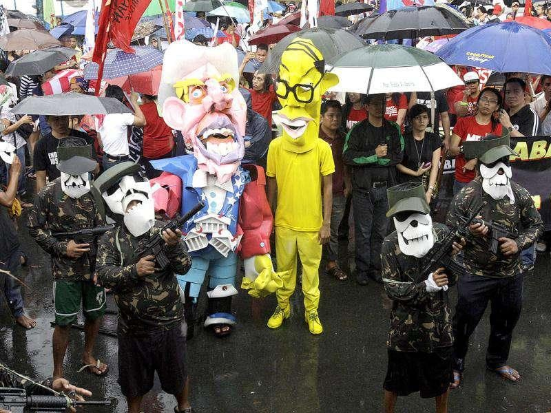 Two performers, one portraying Uncle Sam, left, and another portraying Philippine President Benigno Aquino III, in yellow costume, are surrounded by masked soldier performers during a street play as part of the observance of International Human Rights Day near the presidential palace in Manila, Philippines. Protesters alleged that human rights violation still persist under the present government despite of its promise of reforms. AP/Pat Roque