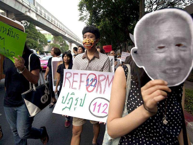 A Thai activist holds a sign calling for the reform of article number 112 in Thailand's Criminal Code as another one holds a mask representing imprisoned Ampon Tangnoppakul as they stage a march against the country's widely-criticised laws protecting the monarchy, in Bangkok on International Human Rights Day. AFP/Joan Manuel Baliellas