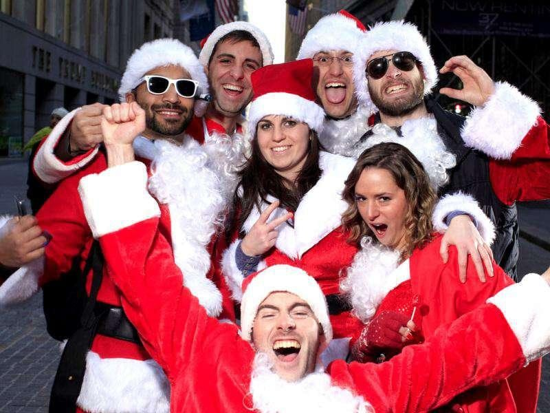 Participants of SantaCon pose for a portrait at the corner of Broad and Wall Street in New York. SantaCon is an annual celebration of the holiday season with revelers travelling around New York to different bars and locations. REUTERS/Carlo Allegri