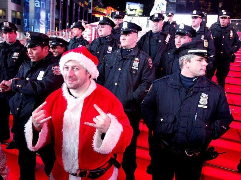 A man dressed in a Santa Claus costume posses for a picture next to police officers in Times Square during the annual SantaCon celebration in New York. REUTERS/Kena Betancur