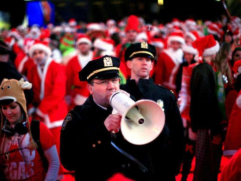 A police officer speaks into a loud hailer near people dressed in Santa Claus costume as they gather in Times Square during the annual SantaCon celebration in New York. REUTERS/Kena Betancur