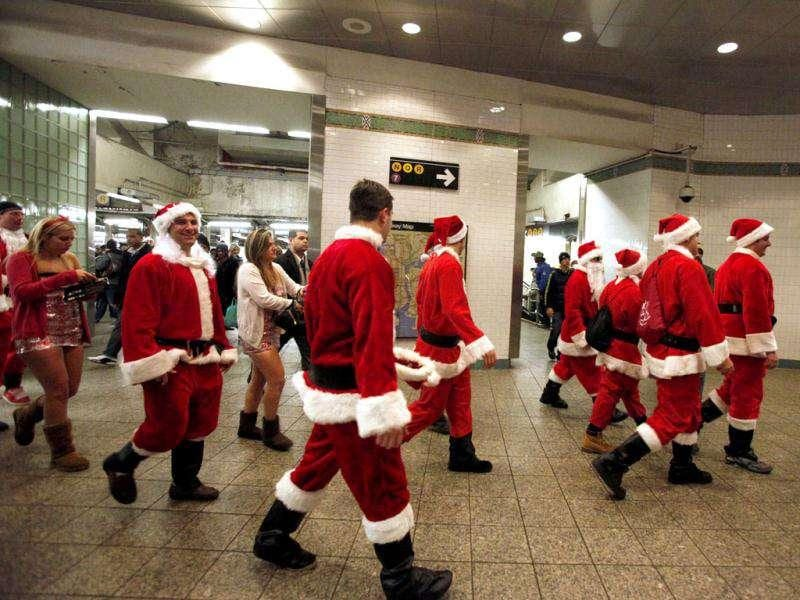 People dressed in Santa Claus costume arrive at Times Square subway station to take part in the annual SantaCon celebration in New York. REUTERS/Kena Betancur
