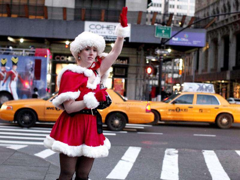 A woman dressed in a female Santa costume hails a cab as she takes part in the annual SantaCon celebration in New York. REUTERS/Kena Betancur