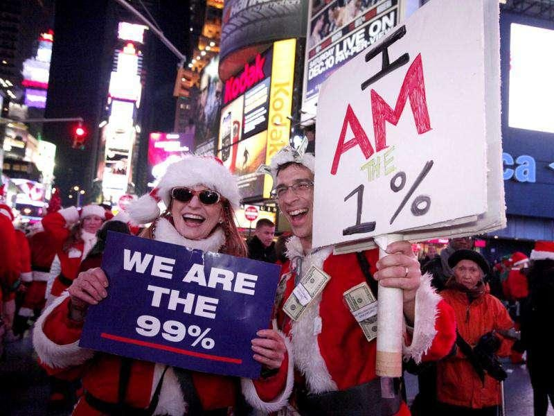 A couple dressed in Santa Claus costume poses for a picture as they hold banners linked with the Occupy Wall Street movement, as they gather in Times Square during the annual SantaCon celebration in New York. REUTERS/Kena Betancur