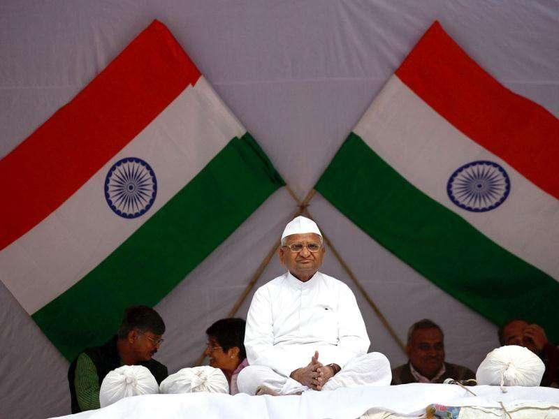 Veteran social activist Anna Hazare sit in front of India's national flags during his day-long fast in New Delhi . REUTERS/Adnan Abidi