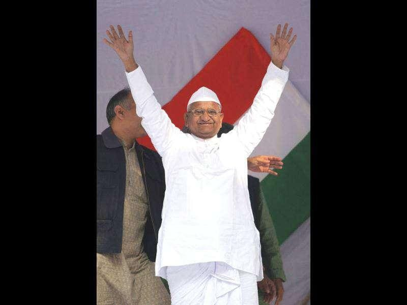 Veteran social activist Anna Hazare waves to his supporters in front of India's national flag during his day-long fast in New Delhi . REUTERS/Adnan Abidi