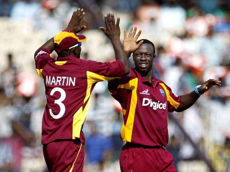 West Indies' bowler Kemar Roach (R), celebrates with teammate Anthony Martin the dismissal of India's batsman Ajinkya Rahane during their fifth one-day international cricket match in Chennai (AP Photo/Aijaz Rahi)