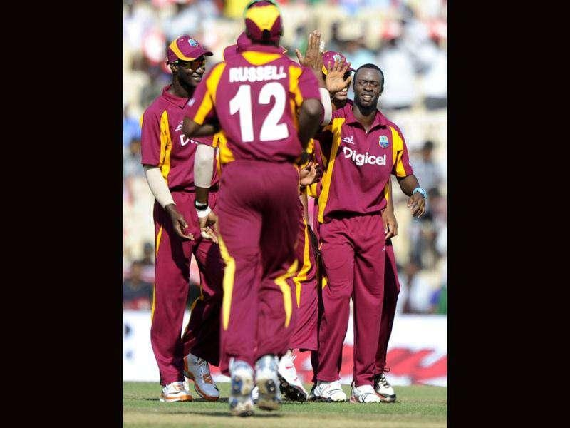 West Indies cricketers congratulate teammate Kemar Roach (R) for taking the wicket of Indian cricketer Parthiv Patel during the final One Day International (ODI) match between India and West Indies at The M.A.Chidambaram Stadium in Chennai. AFP/Dibyangshu Sarkar