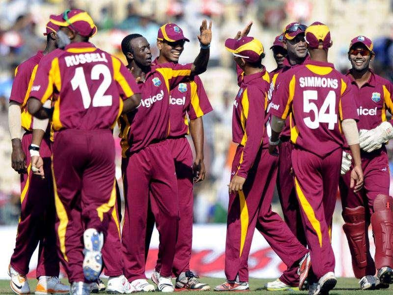 West Indies cricketers congratulate teammate Kemar Roach (3rd L) for taking the wicket of Indian cricketer Parthiv Patel during the final One Day International (ODI) match between India and West Indies at The M.A.Chidambaram Stadium in Chennai. AFP/Dibyangshu Sarkar