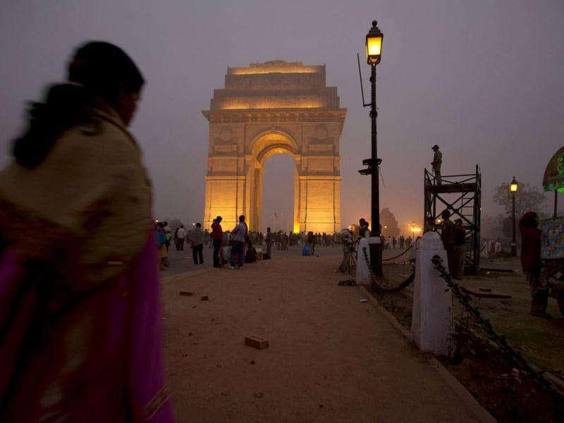 A policeman stands guard as tourists walk near the landmark India gate in New Delhi. AP Photo/Manish Swarup