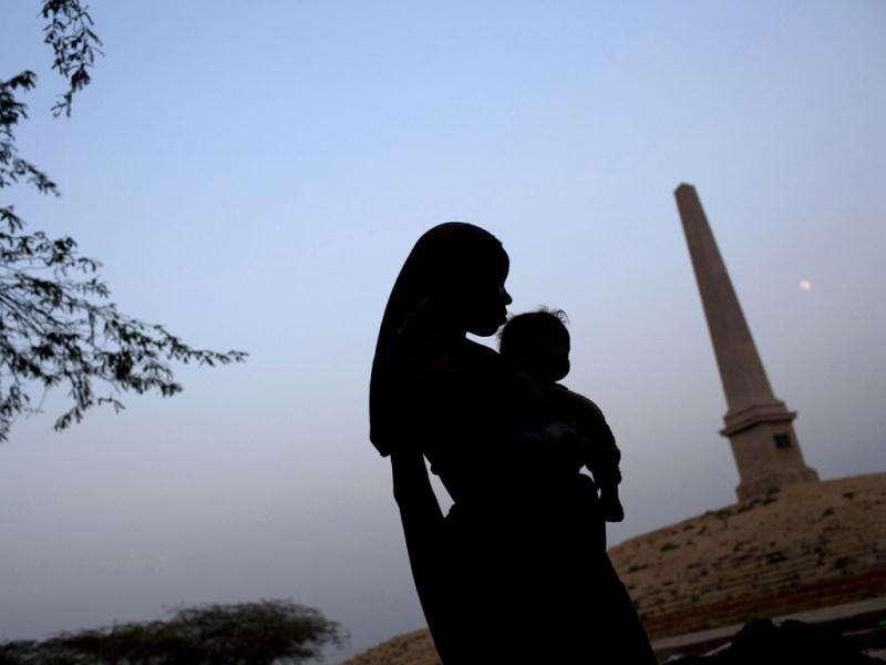 A woman laborer holds her child near the Obelisk, built to mark where Britain's King George V sat at the site of the 1911 Coronation Durbar in New Delhi. AP Photo/Kevin Frayer