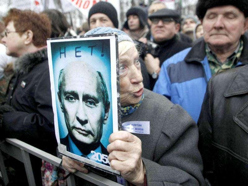 An elderly demonstrator holds a poster showing an edited photo of Prime Minister Vladimir Putin and signed