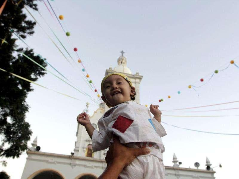 A child smiles outside the Basilica de Guadalupe in San Salvador. Thousands of Salvadoran pilgrims celebrate the Day of the Virgin of Guadalupe on December 12. Reuters/Luis Galdamez