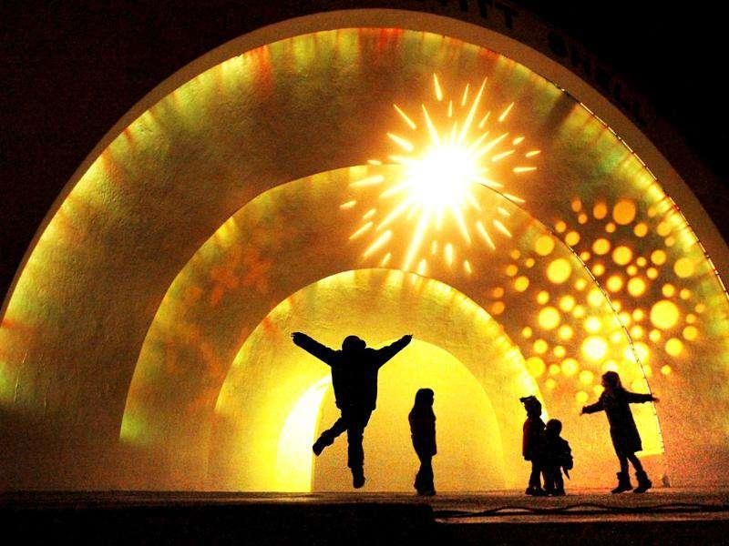 Children jump on stage to dance during the Brooks Museum of Art light festival in Memphis. (AP Photo/The Commercial Appeal, Jim Weber)