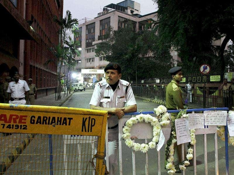 Policemen stand guard as flowers and messages put by mourners in memory of those who died in AMRI fire are seen on a barricade outside the AMRI Hospital, in Kolkata.