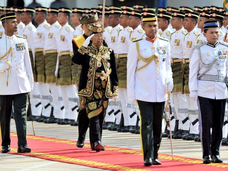 The 14th king of Malaysia, Sultan Abdul Halim Mu'adzam Shah (C), salutes the royal guard of honour during the king's welcoming ceremony at the Parliment House in Kuala Lumpur. AFP/Mohd Rasfan
