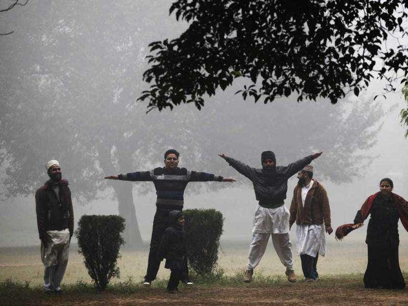 People perform stretch exercises on a foggy morning in Allahabad. AP Photo