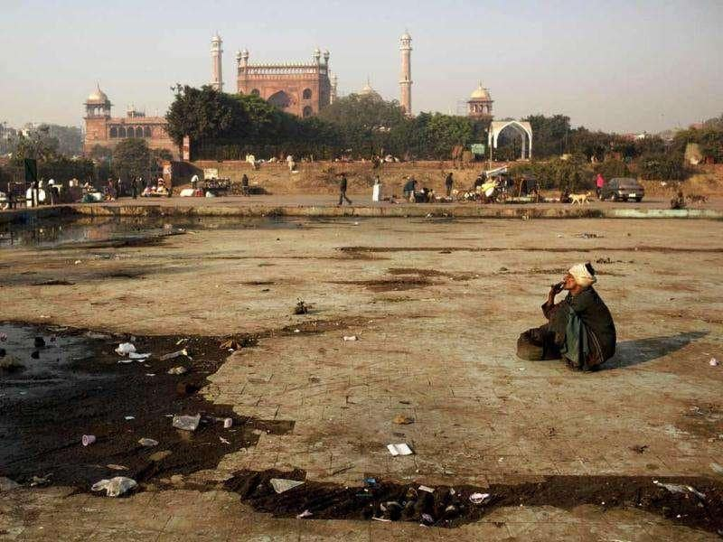 A man smokes in a dry fountain in front of Jama Masjid in New Delhi. AP Photo