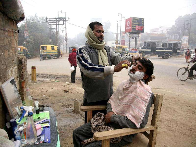A barber gives a shave to a customer in a foggy morning in Allahabad. AP Photo